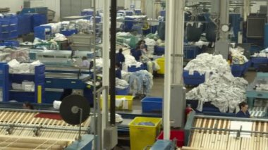Workers feed garments into machines — Stock Video