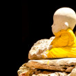 Little buddha statue on the rock and black background — Stock Photo #56932671