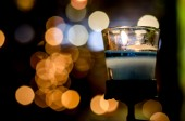 Blue candle in the night mood on bokeh background — Stock Photo