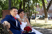 Bride and groom sitting on a bench — Stock Photo