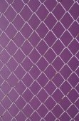 Wire Mesh, iron wire fence on the wall purple background. — Stock Photo