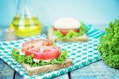 Sandwich with mozzarella, tomatoes and lettuce — Stock Photo