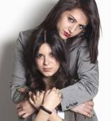 Sisters looking and hugging — Stock Photo