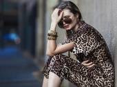 Weak woman sitting in the city and wearing a leopard-skin dress — Stok fotoğraf
