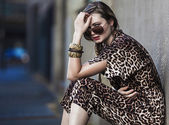Weak woman sitting in the city and wearing a leopard-skin dress — ストック写真