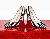 Woman shoes on red furniture — Stockfoto