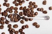 Teaspoon and coffee beans on white — Stock Photo