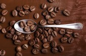 Teaspoon and coffee beans on wood — Stock Photo