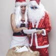 Beautiful girl and Santa Claus reading a Christmas letter — Stock Photo #58364609