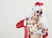 Female Santa Claus unwrapping a gift — Stock Photo