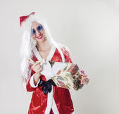 Happy Santa Claus unwrapping a gift — Stock Photo