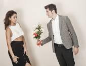 Hombre que a una mujer hermosa y ofreciéndole un ramo de flores — Foto de Stock