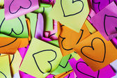 Colorful post-it texture with drawn hearts — Stock Photo