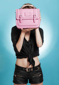 Beautiful girl holding and hiding behind a pink bag — Stock Photo