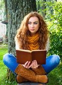 Ginger-haired woman reading a book in park sitting on the bench — Stock Photo
