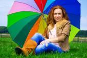 Açık havada bir gökkuşağı şemsiye ile gülümseyen güzel kadın — Stok fotoğraf