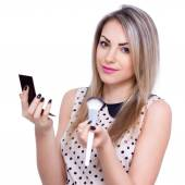 A portrait of a young woman with a mirror and brush over white backgroun — Stock Photo