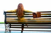 Red - haired woman sitting alone on bench with boo — Stock Photo