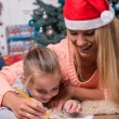 Mom and daughter waiting for Christmas — Stock Photo #56658489