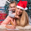 Mom and daughter waiting for Christmas — Stock Photo #56659879