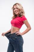 Slim waist of young woman in big jeans showing successful weight — Stock Photo