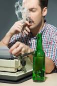 Author smoking cigar and drinking alcohol at typewriter — Zdjęcie stockowe