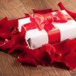 Present box in rose petals on wooden background — Stock Photo #62636443