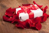 Caja presente en pétalos de rosa sobre fondo de madera — Foto de Stock