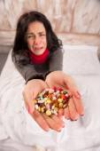 Frustrated woman lying in bed with pills — Stock Photo