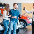 Sales consultant gives keys from new car to young couple — Stock Photo #68171037