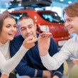 Salesman demonstrates toy car model to customers — Stock Photo #68171333