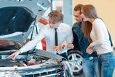 Sales consultant shows technical characteristics of the vehicle — Stock Photo