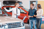 Customers communicate with sales consultant about the car — Stockfoto