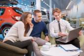 Couple communicating with the salesman in showroom — Stock Photo