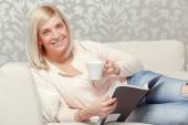 Woman reads magazine at home — Stock Photo