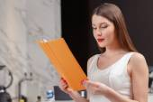 Woman holds a menu at the bar — Stock Photo