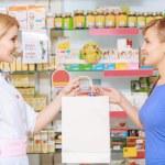 Pharmacy chemist and customer at the drugstore — Stock Photo #69514159