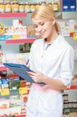 Druggist makes notes in a clipboard — Stock Photo