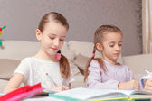 Two girls write in their exercise books — Stock Photo