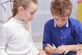 Boy and girl knit a bracelet — Stock Photo