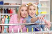 Saleswoman and customer choose clothes — Stock Photo