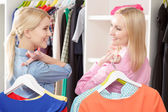 Sales woman and a customer with hangers — Stock Photo