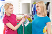 Customer talks to sales consultant by the clothing rack — Fotografia Stock