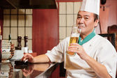 Cook has a drink in restaurant kitchen — Stock Photo