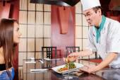 Cook serves dish to a client — Stock Photo