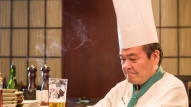 Satisfied Japanese chef sitting in kitchen — Stock Video