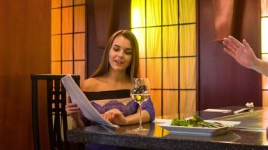 Attractive young smiling woman sitting at table in chic restaurant — Stock Video