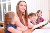 Young teacher reading to pupils — Stock Photo