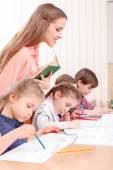 Teacher checking work of pupils — Stock Photo