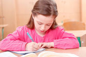 Little writing girl during classes — Stock Photo